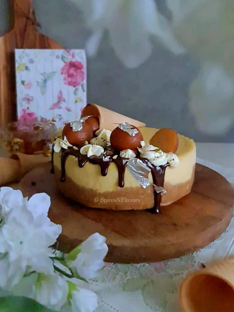 baked cheesecake placed on a wooden board with flowers in the foreground