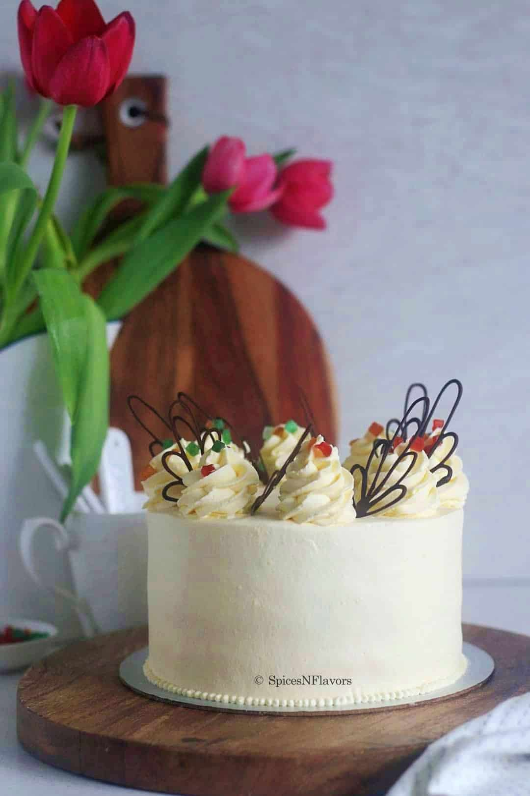 pineapple cake placed on a round wooden board with flowers in the background
