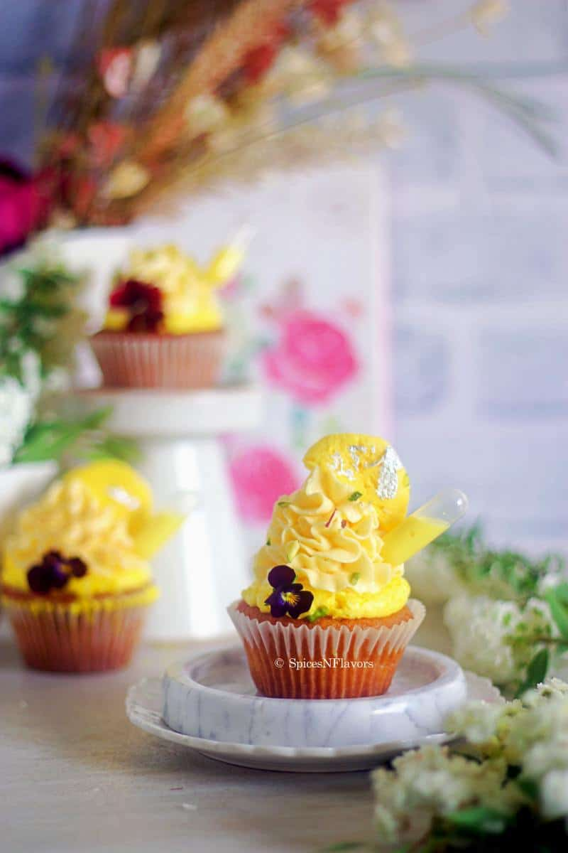 image of cupcake placed on marble coaster with few more cupcakes in the background