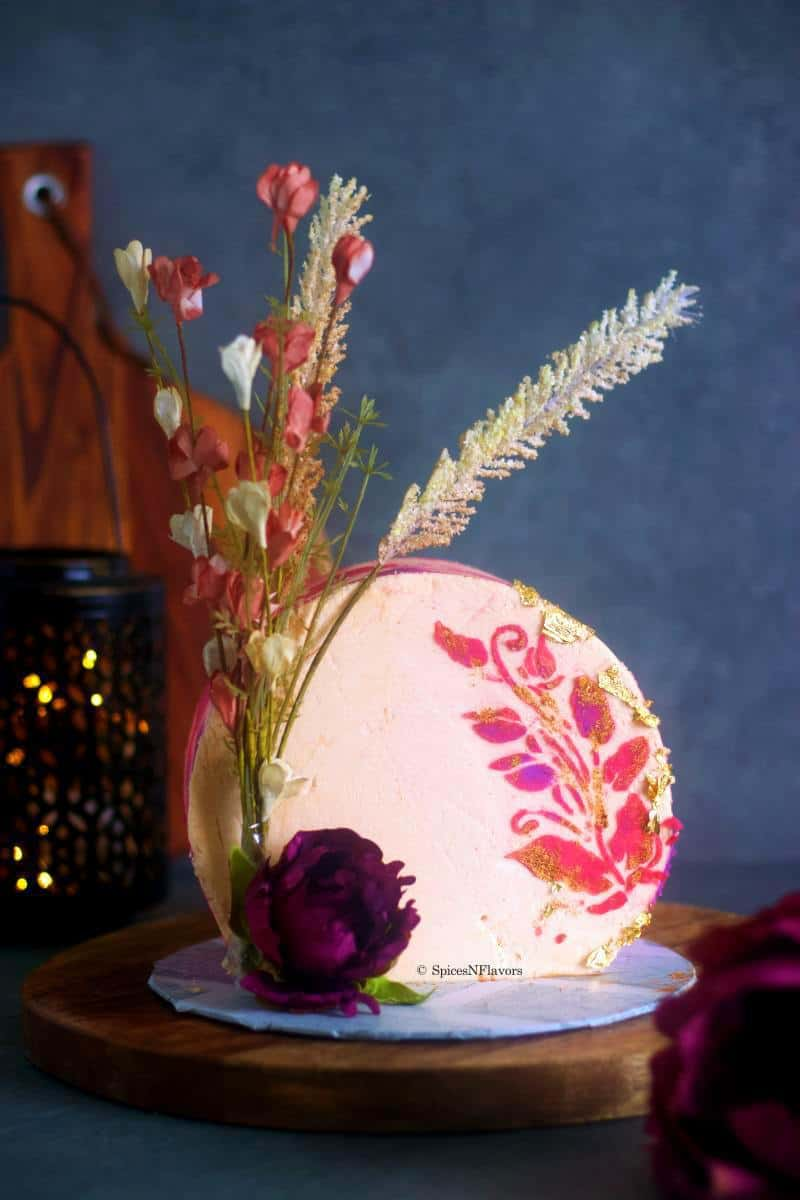 front view of the decorated cake placed on a cake board showing all the details of dried flowers and buttercream stenciling