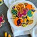 mehendi cookies of different shapes placed on a white plate